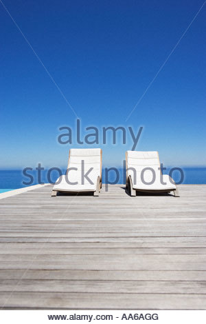 Folding chairs on infinity pool deck - Stock Photo
