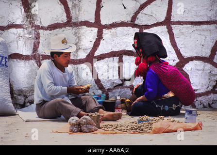 A ZINACANTAN MAYAN INDIAN COUPLE PREPARE BAGS OF MONKEY NUTS AT A MARKET IN SAN LORENZO ZINACANTAN CHIAPAS MEXICO - Stock Photo