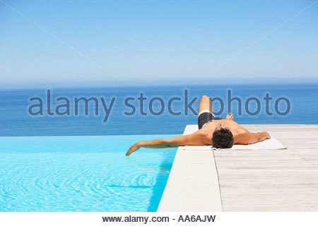 Man on infinity pool deck in swimsuit - Stock Photo