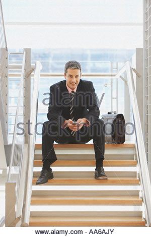 Businessman on staricase with cell phone - Stock Photo