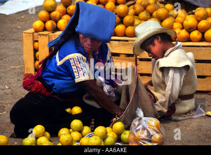 WOMAN WITH HER SON SELLING FRUIT AT THE MARKET PLACE IN SAN JUAN CHAMULA CHIAPAS MEXICO - Stock Photo