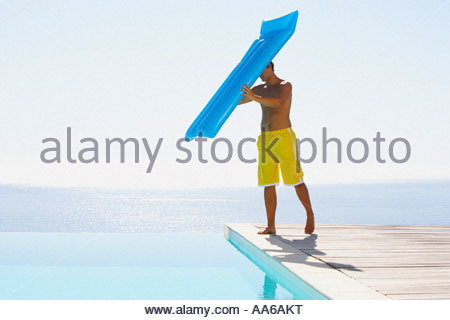 Man on infinity pool deck in swimsuit with flotation device - Stock Photo