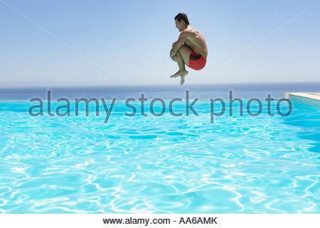 Man leaping into infinity pool - Stock Photo