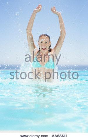 Woman in bikini splashing and smiling in pool - Stock Photo