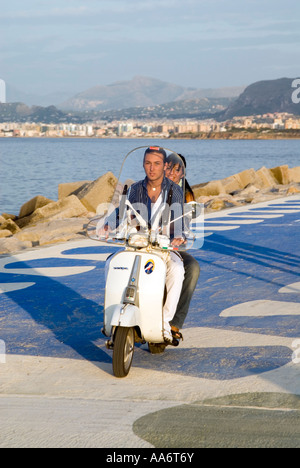 Young couple riding a Vespa beside the sea, Palermo, Sicily Italy - Stock Photo