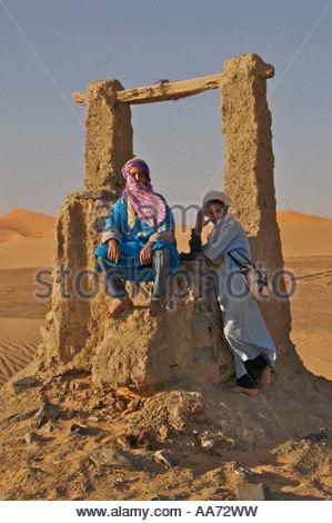 Tuareg Berber boys by old water well Saharan Desert Morocco - Stock Photo