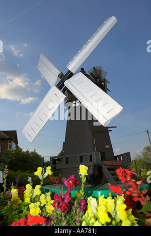 wooden model of dutch windmill with red and yellow flowers in foreground and blue sky - Stock Photo