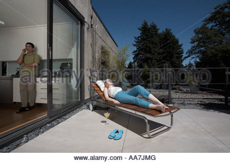 Young woman laying on lounge chair - Stock Photo