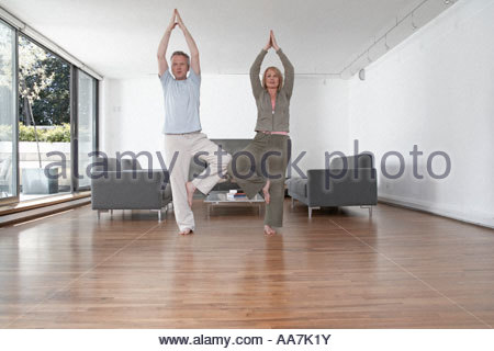Middle-aged couple practicing yoga - Stock Photo