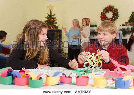 Teenagers making Christmaas snowflakes - Stock Photo