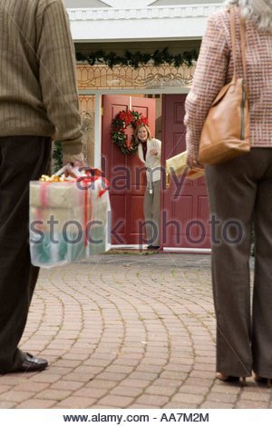 Man and woman arriving with Christmas presents - Stock Photo