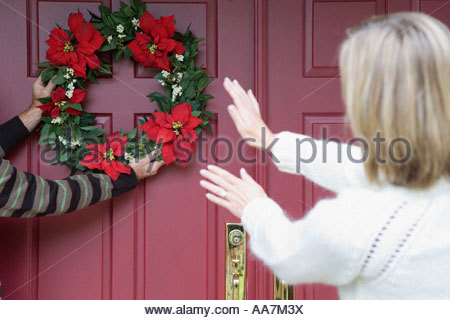 Woman directing person hanging Christmas wreath - Stock Photo