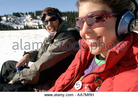 Couple wearing headphones in the snow - Stock Photo