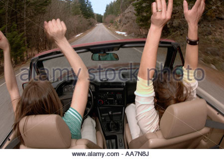 Women driving convertible with no hands - Stock Photo