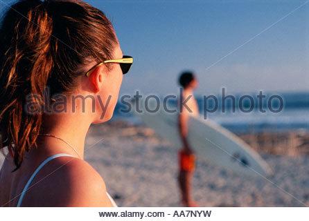 Woman admiring surfer on beach - Stock Photo