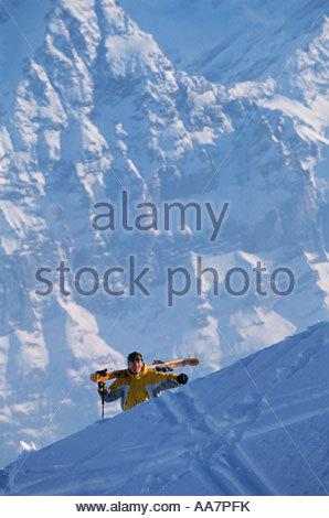 Skier climbing mountain carrying skis - Stock Photo