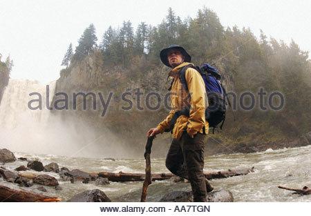 Man hiking near waterfall - Stock Photo