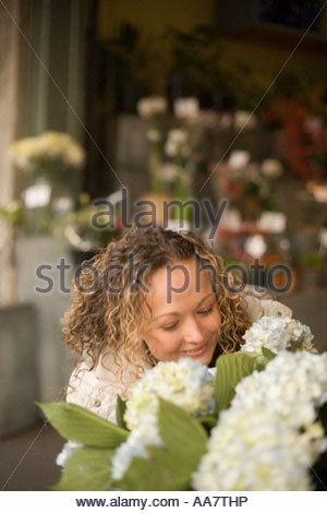 Young woman smelling flowers for sale - Stock Photo