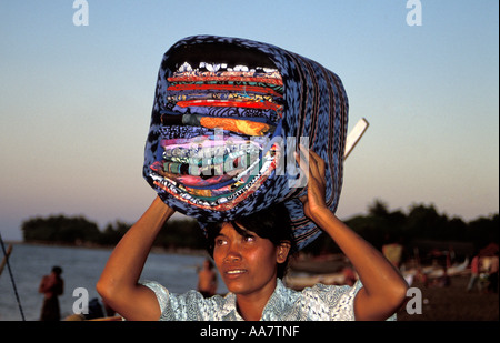 Female Hawker balancing textiles on head, Lovina Beach, Bali, Indonesia - Stock Photo