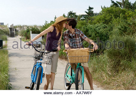 Adult couple with bicycles kissing on path - Stock Photo