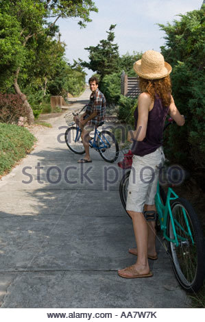 Adult couple with bicycles on beach path - Stock Photo