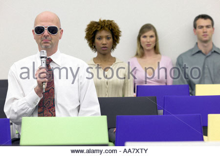 Businessman in sunglasses talking into microphone - Stock Photo