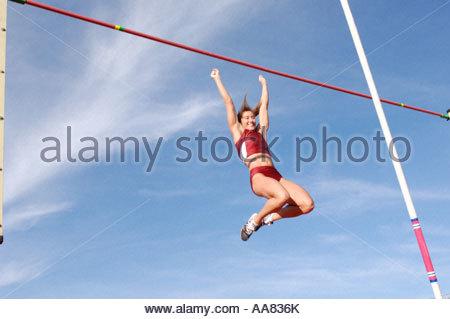 Female athlete pole vaulting - Stock Photo