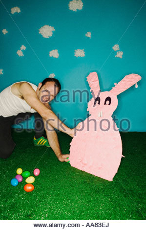 Man pushing over Easter bunny - Stock Photo