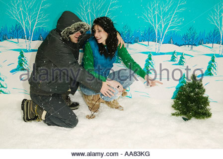 Couple pointing at miniature Christmas tree - Stock Photo