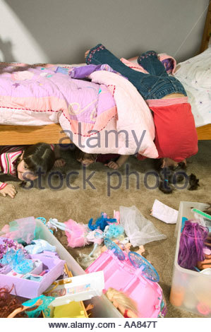 Young girls hiding under the bed - Stock Photo