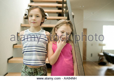 Sisters standing on staircase - Stock Photo