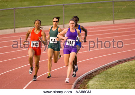 Four young adult women on running track - Stock Photo