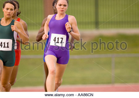 Close-up of four young adult women athletes running - Stock Photo