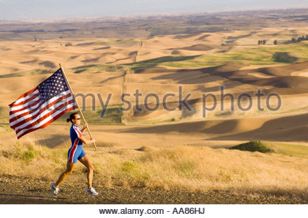 Female athlete with American flag on roadside - Stock Photo