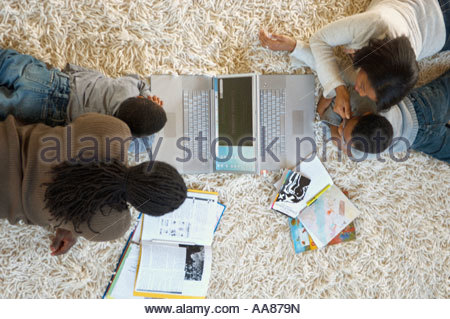 Family using laptops and doing homework on shag rug - Stock Photo