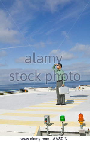 Businessman standing on helicopter landing pad - Stock Photo
