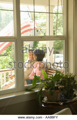 Hispanic military solder and wife sitting on porch swing - Stock Photo