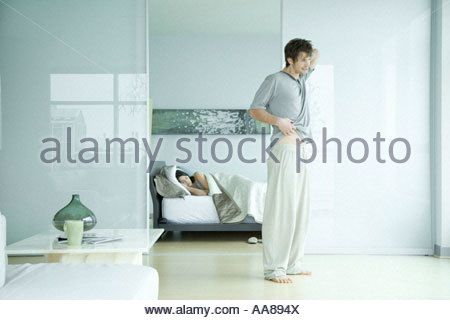 Young adult man stretching in front of bedroom - Stock Photo