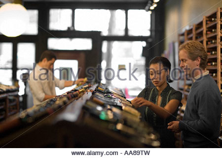 Sales clerk with man in liquor store - Stock Photo