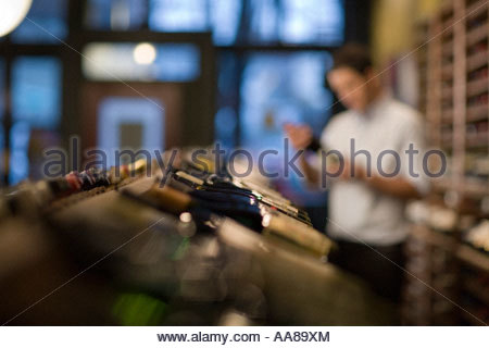 Wine bottles in liquor store with man in background - Stock Photo