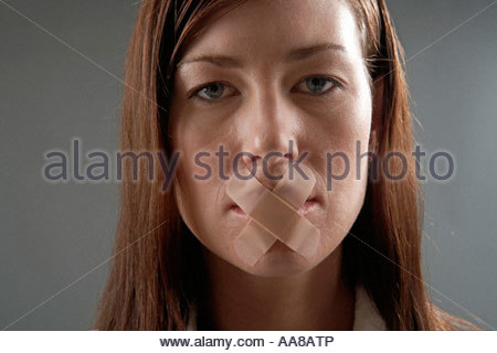 Young woman with bandaids over her lips - Stock Photo