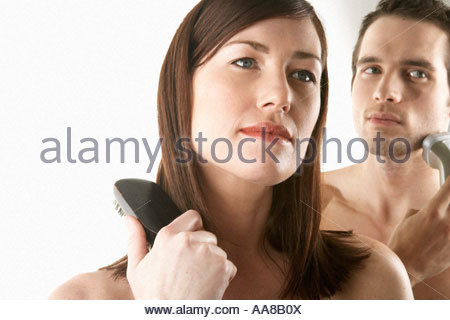 Young woman brushing her hair with man in background shaving - Stock Photo