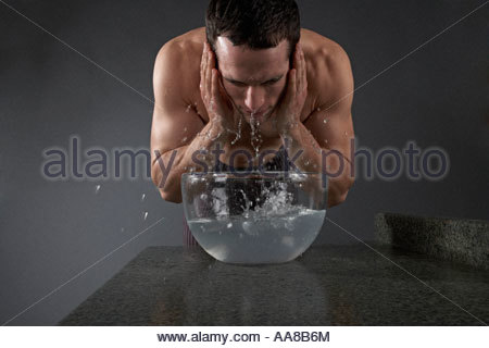 Young man washing his face - Stock Photo