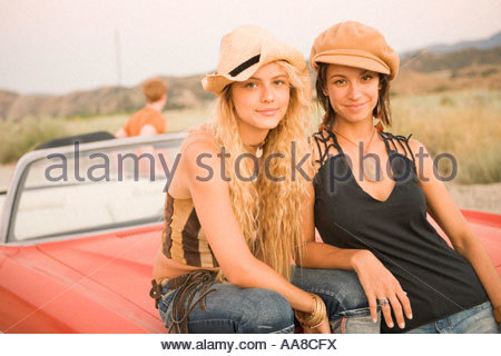 Two young women sitting on hood of car - Stock Photo