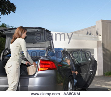 Mother unloading groceries from car - Stock Photo