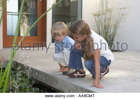Children looking at pond - Stock Photo