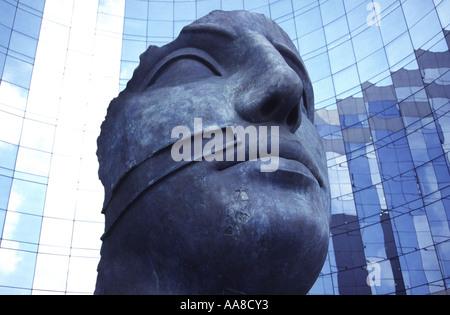 A bronze sculpture by Igor Mitoraj looks on at the glass clad skyscrapers of Paris' La Defense District. - Stock Photo
