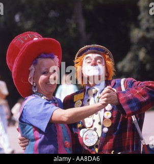 Smiling middle aged woman dancing with clown - Stock Photo