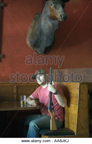 Man with rifle sitting under deer head - Stock Photo