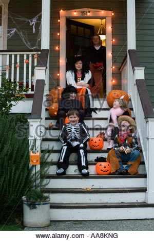 Children costumed for Halloween sitting on porch - Stock Photo